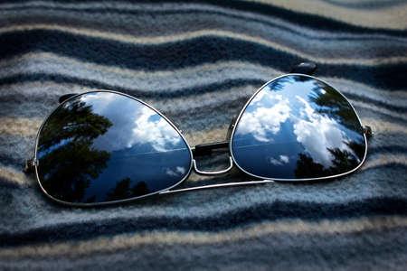 mirrored: mirrored sunglasses reflecting the sky