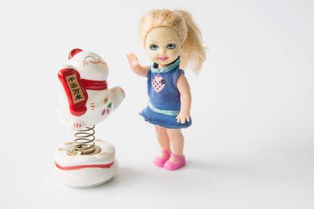 stride: Little girl doll with a maneki Neko on white background Editorial