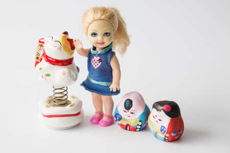 stride: Little girl doll with some mini figurines on white background Editorial