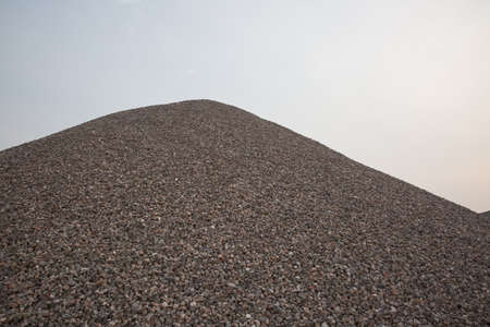 landfill site: Of gravel crushed Pile stone outdoors with cloudy blue sky background Stock Photo