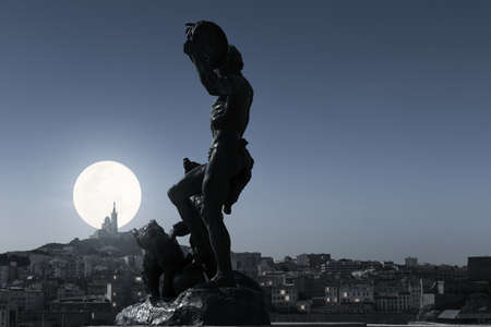 Cityscape of Marseille at night. Louis Botinelly's bronze sculpture