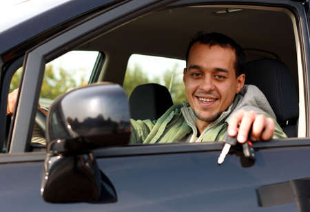 new age: Happy young man sitting ina new car holding out keys
