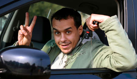 Young man showing car keys and Victory sign. photo