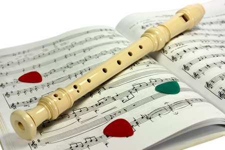 Flute (recorder) lying on notes sheet with several guitar pick-ups photo