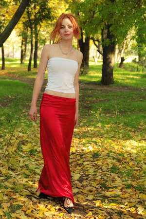 Beautiful girl in red, walking in a park photo