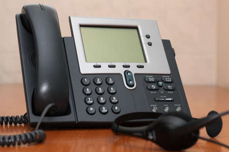IP Phone close-up view with blurred headset on foreground Stock Photo