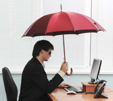 Information security concept- young buisnessman holding an umbrella upon his workstation. Stock Photo