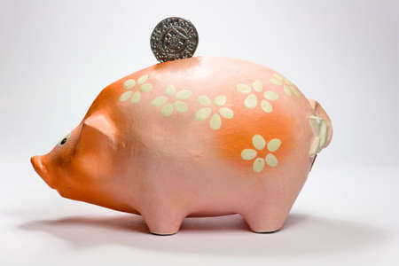 Ruddy piggy bank made of clay isolated on white background photo