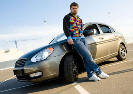Young man holding keys of his new car photo