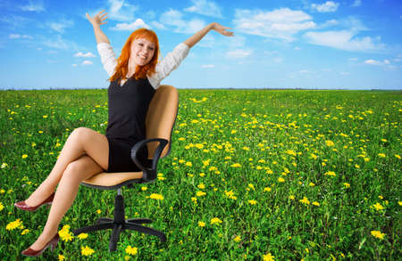 Cheerful businesswoman on a beautiful meadow full of flowers photo