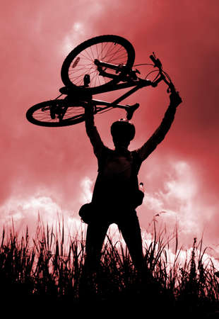 Silhouette of a biker holding his bicycle, red tint photo