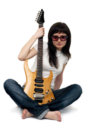 Pretty young girl sitting and holding an electric guitar photo