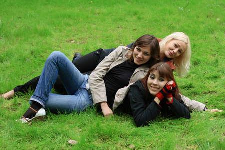 Company of girls having fun on green grass photo