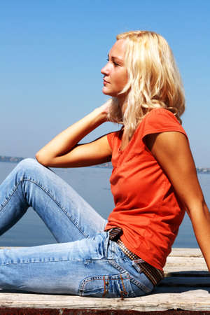foot bridge: Cute girl sitting on a river bank on a sunny day