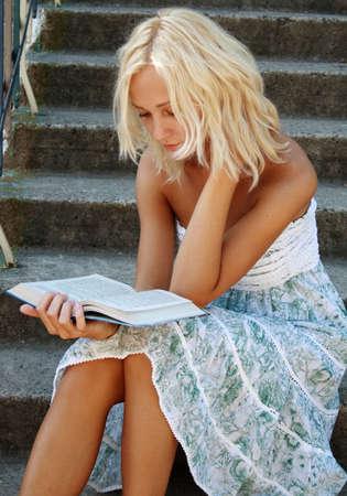 Cute blonde girl reading a book