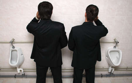 mensroom: Two businessman talking by mobile phones in a WC