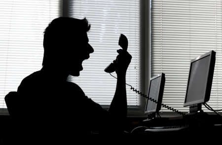 Silhouette of an angry man shouting into the phone receiver in his office Stock Photo