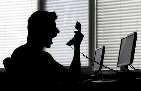 jefe enojado: Silueta de un hombre enojado gritando en el tel�fono receptor en su oficina