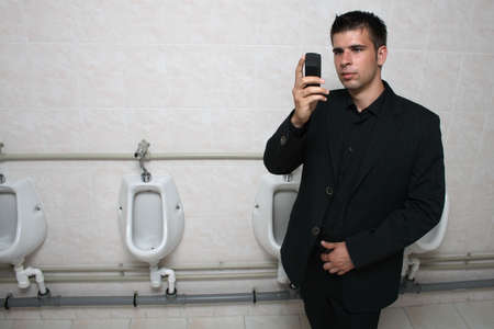 mensroom: Businessman holding his mobile phone in a toilet, taking picture of himself.