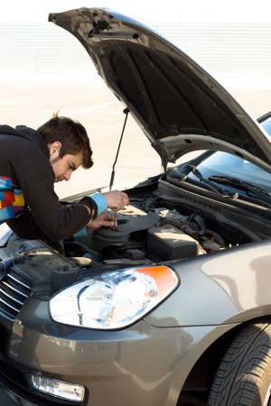 Car driver examining the car's engine on a parking Stock Photo - 4940726