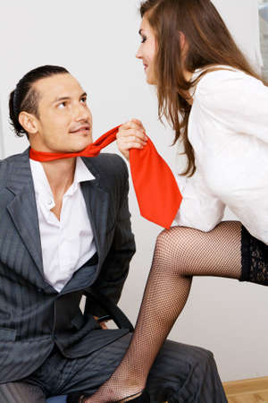 subordinate: Young businessman and businesswoman flirting in office