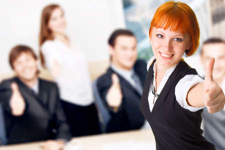 Business people showing thumbs up, with pretty redhead lady on foreground photo
