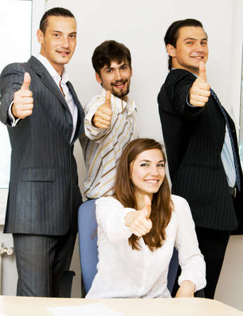 Successful business team showing thumbs up, focus on woman on foreground photo