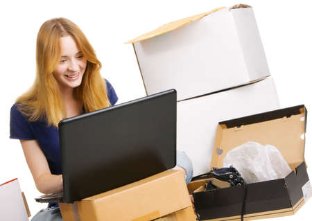 Young beautisul woman surrounded by delivered orders, surfing an online store at her laptop photo