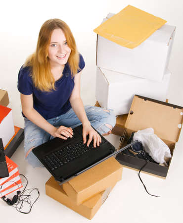 Young beautisul woman surrounded by delivered orders, surfing an online store at her laptop