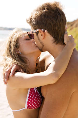 Young beautiful couple kissing at the sea shore photo