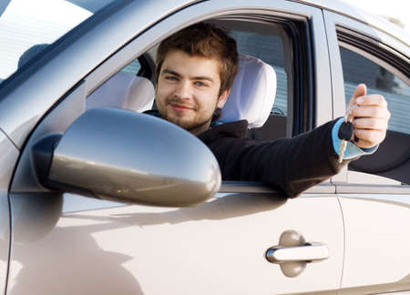 Young man driving his new car, holding out keys Stock Photo