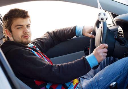 hombre conduciendo: Un joven conduc�a su coche nuevo