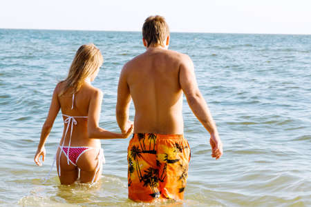 guy on beach: Young beautiful couple going to swim