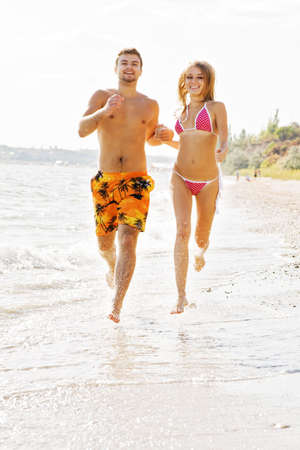 Young cheerful couple running along the beach photo