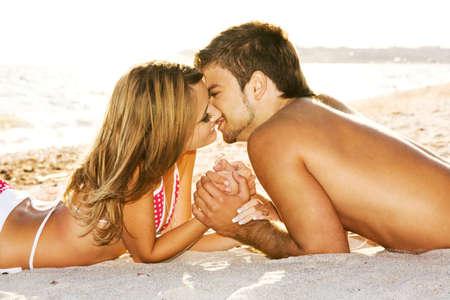 pareja besandose: Pareja rom�ntica besar en la orilla del mar