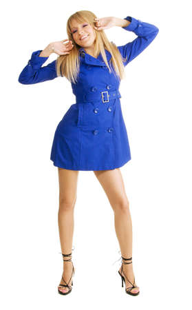 Pretty young woman in a blue coat stretching herself photo