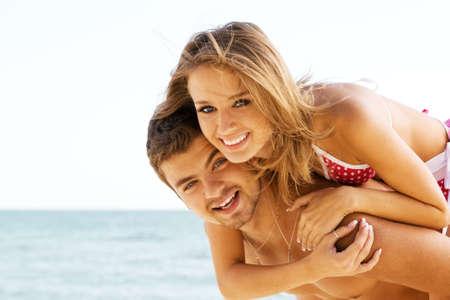 Beautiful young couple having fun on the seaside photo