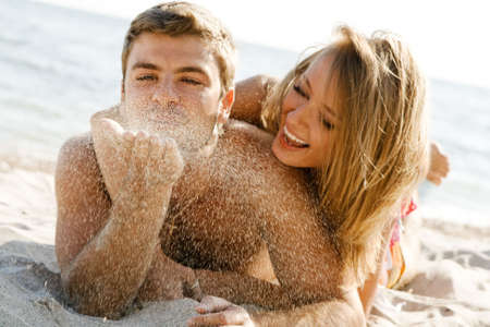 blows: Romantic couple having fun on the seaside, focus on the sand grains