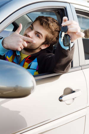 Happy young man sitting ina new car holding out keys photo