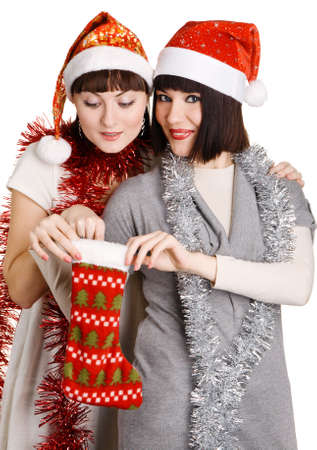 Two girls in christmas hats taking out presents, white background photo
