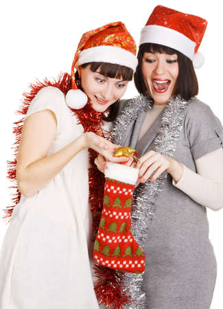 Two funny girls taking out their christmas presents, white background photo