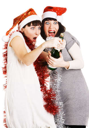 Two funny girls in christmas hats opening a champagne bottle photo