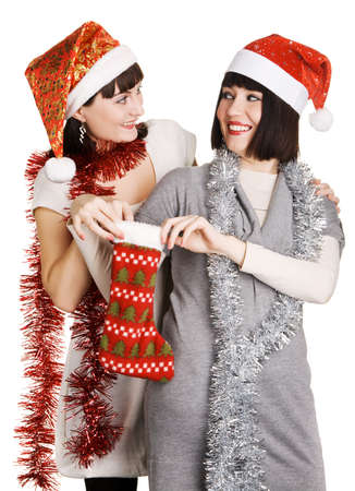 Two young women taking out their Christmas presents from a sock photo
