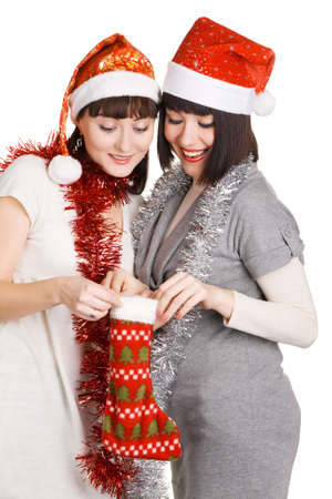 Two cheerful girls in Santas hats taking out their christmas presents photo
