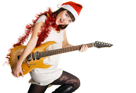 Expressive young woman in Santas hat playing an electric guitar