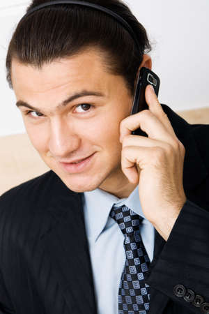 Cheerful young businessman holding a mobile phone photo