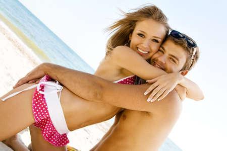 beach blond hair: Young cheerful couple having fun on the beach on a sunny day