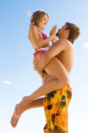 Young cheerful couple having fun on the beach on a sunny day photo