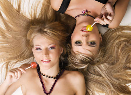 Two beautiful girls with bright makeup licking lollipops photo