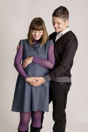 Beautiful pregnant woman with her husband studio portrait photo